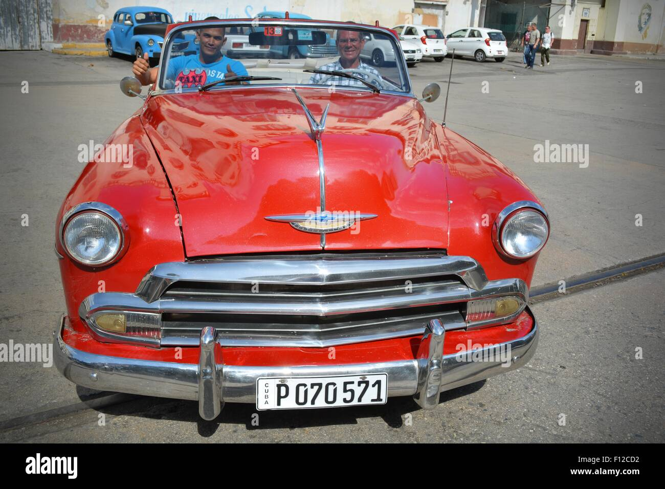 Gleaming red, vintage, soft top taxi, with driver and passenger ready to depart from parking lot in Havana, Cuba - Stock Image