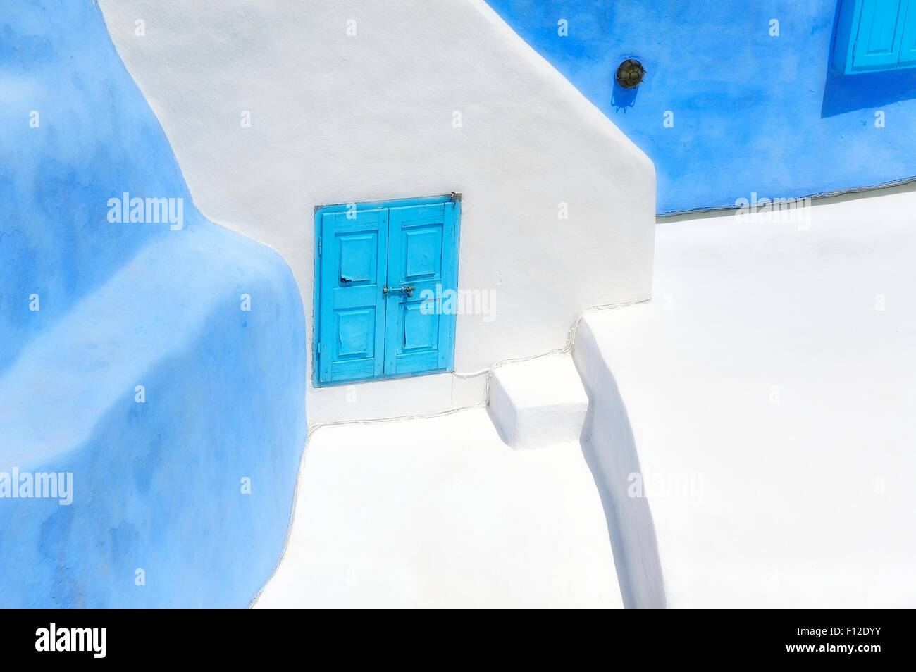 An abstract painted building with blue shuttered windows.Santorini Greece - Stock Image