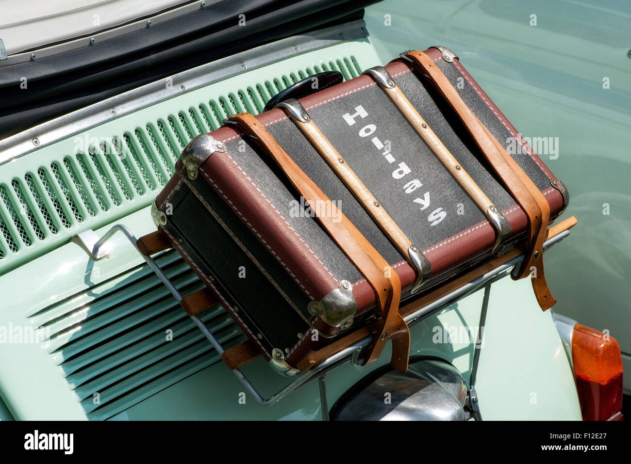 Suitcase strapped to the back on top of the boot of a vintage car - Stock Image