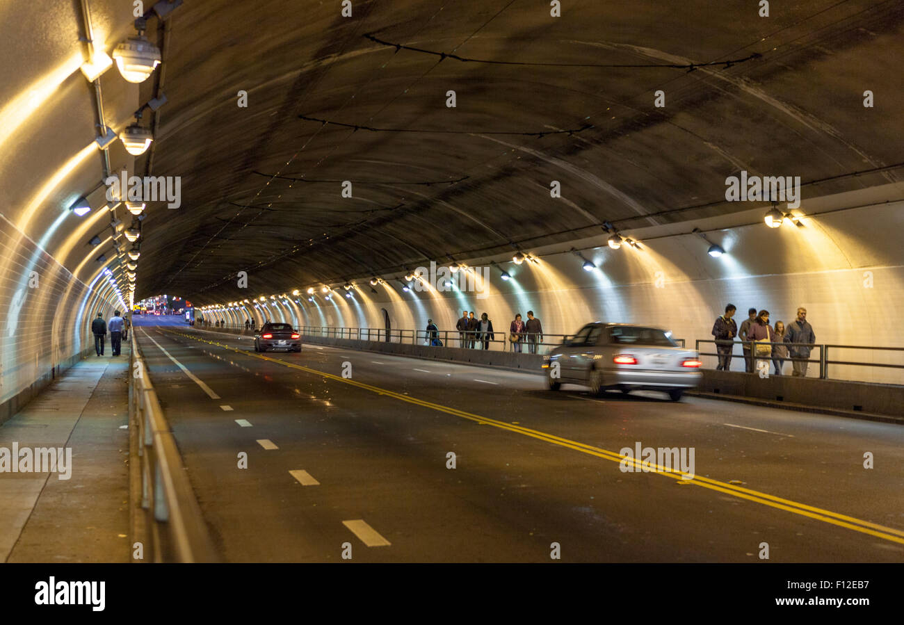 Pedestrians and cars move in a blur through the Stockton St tunnel in San Francisco, California - Stock Image