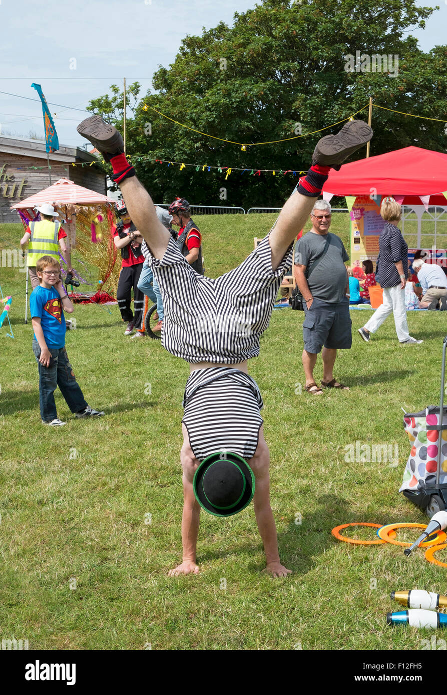 a childrens entertainer doing a handstand - Stock Image