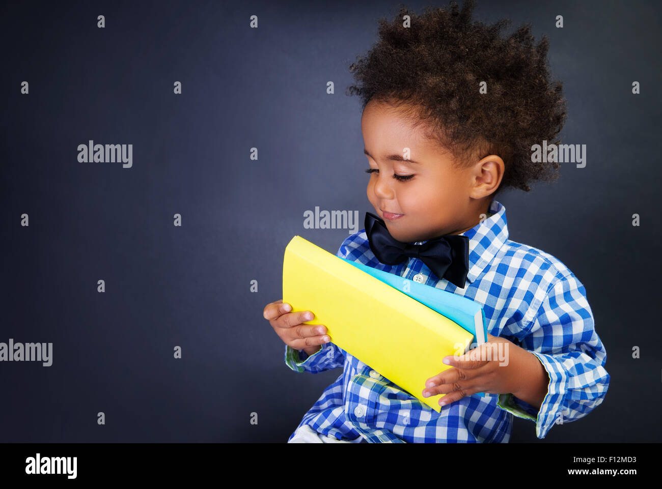 Cute little schoolkid with books in hands over blackboard background, preparing to go to first grade - Stock Image