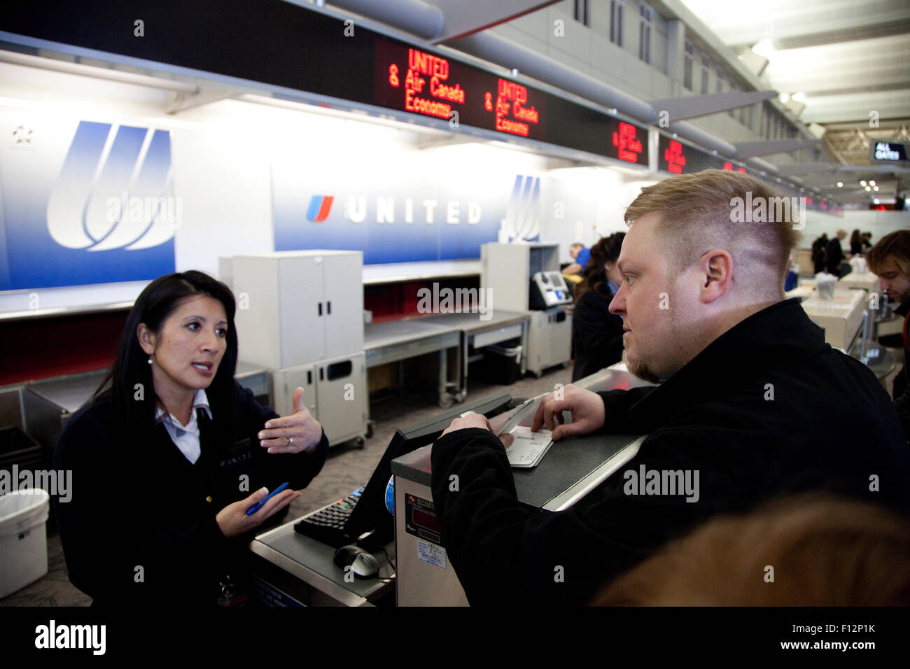 Airline counter clerk gesturing with her hands helping passenger with his check in. Minneapolis Minnesota MN USA - Stock Image
