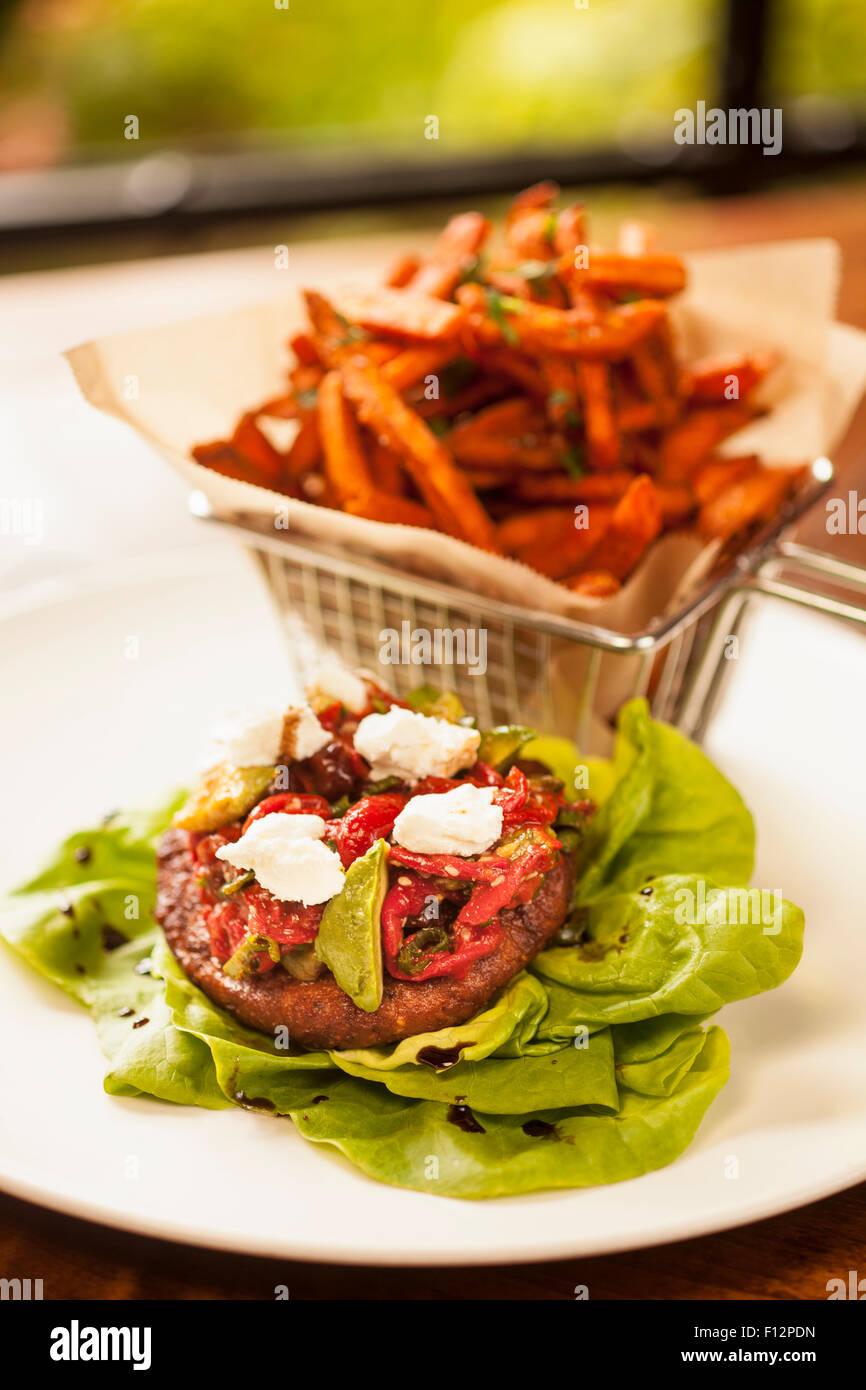 sweet potato quinoa burger on a lettuce wrap, goat cheese, avocado and cranberry piquillo relish with sweet potato - Stock Image