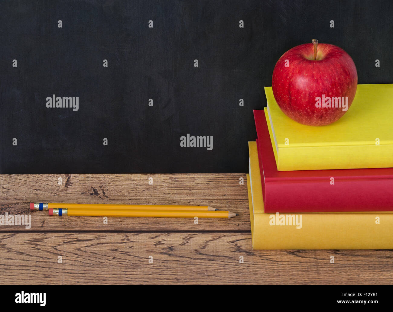 Stack Of School Books With Apple And Pencils On The Desk Chalkboard In Background Copy Space