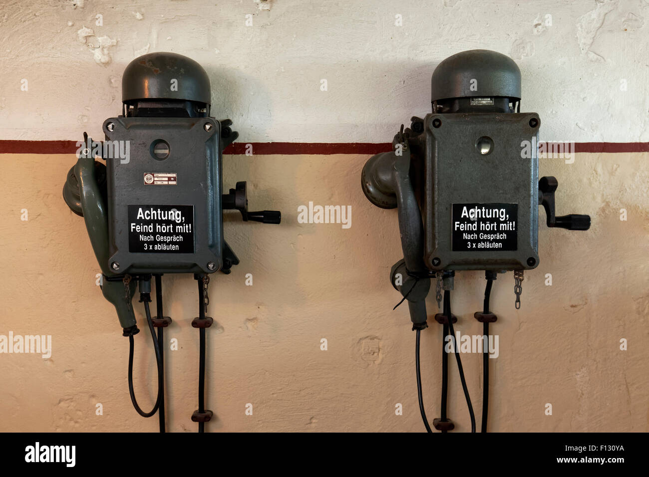 Two telephones in a bunker from the 2nd World War with inscription, the enemy is listening, in German - Stock Image