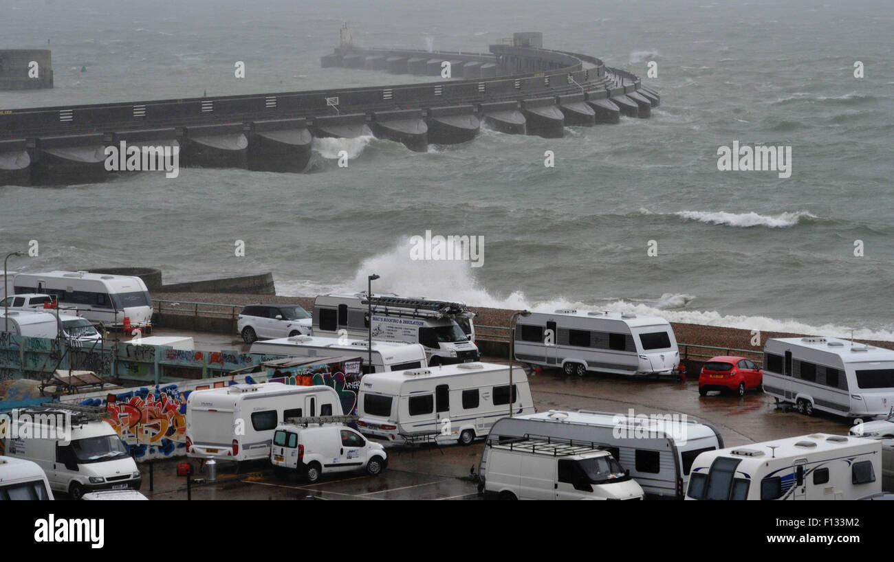 Brighton, UK. 26th August, 2015. UK weather. Waves crash over Brighton Marina behind where a group of travellers - Stock Image