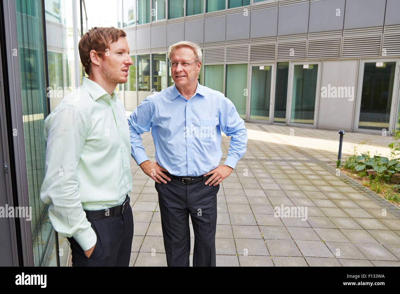 Business men talking to each other during lunch break outside the office - Stock Image