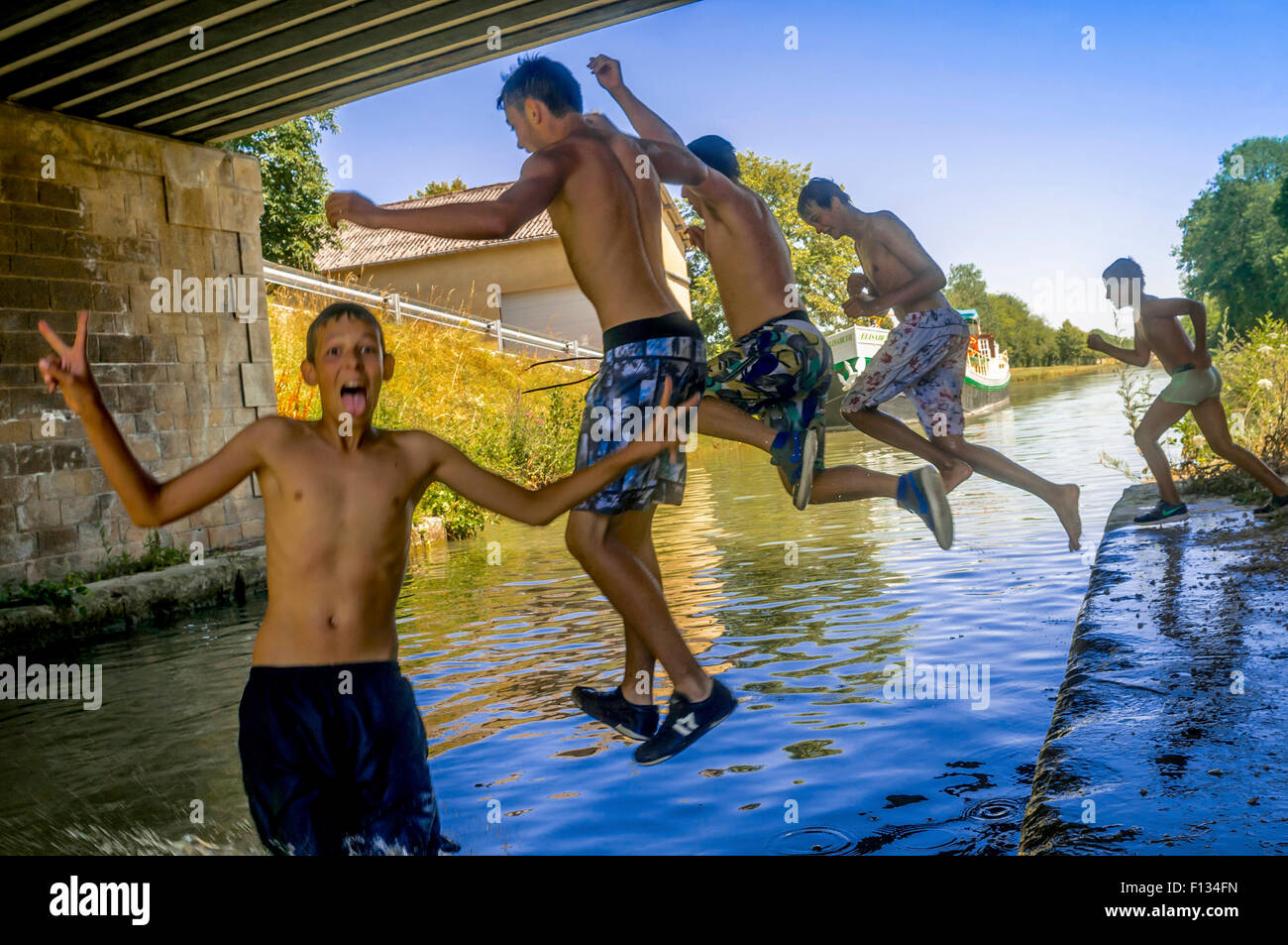 French youths jumping into canal, Yonne, France - Stock Image