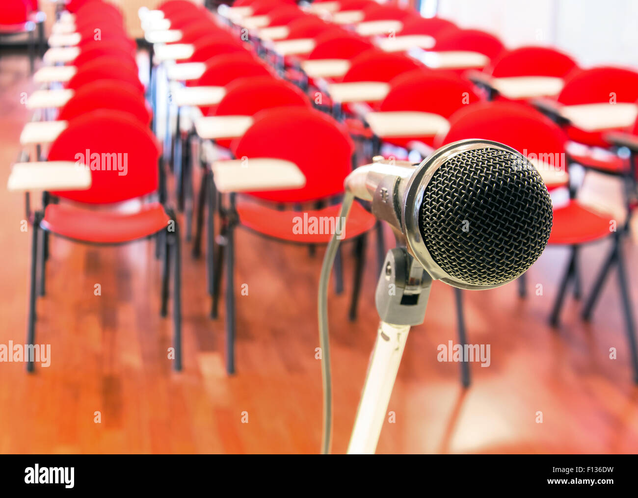 Close up of microphone in front of empty chairs in conference room - Stock Image