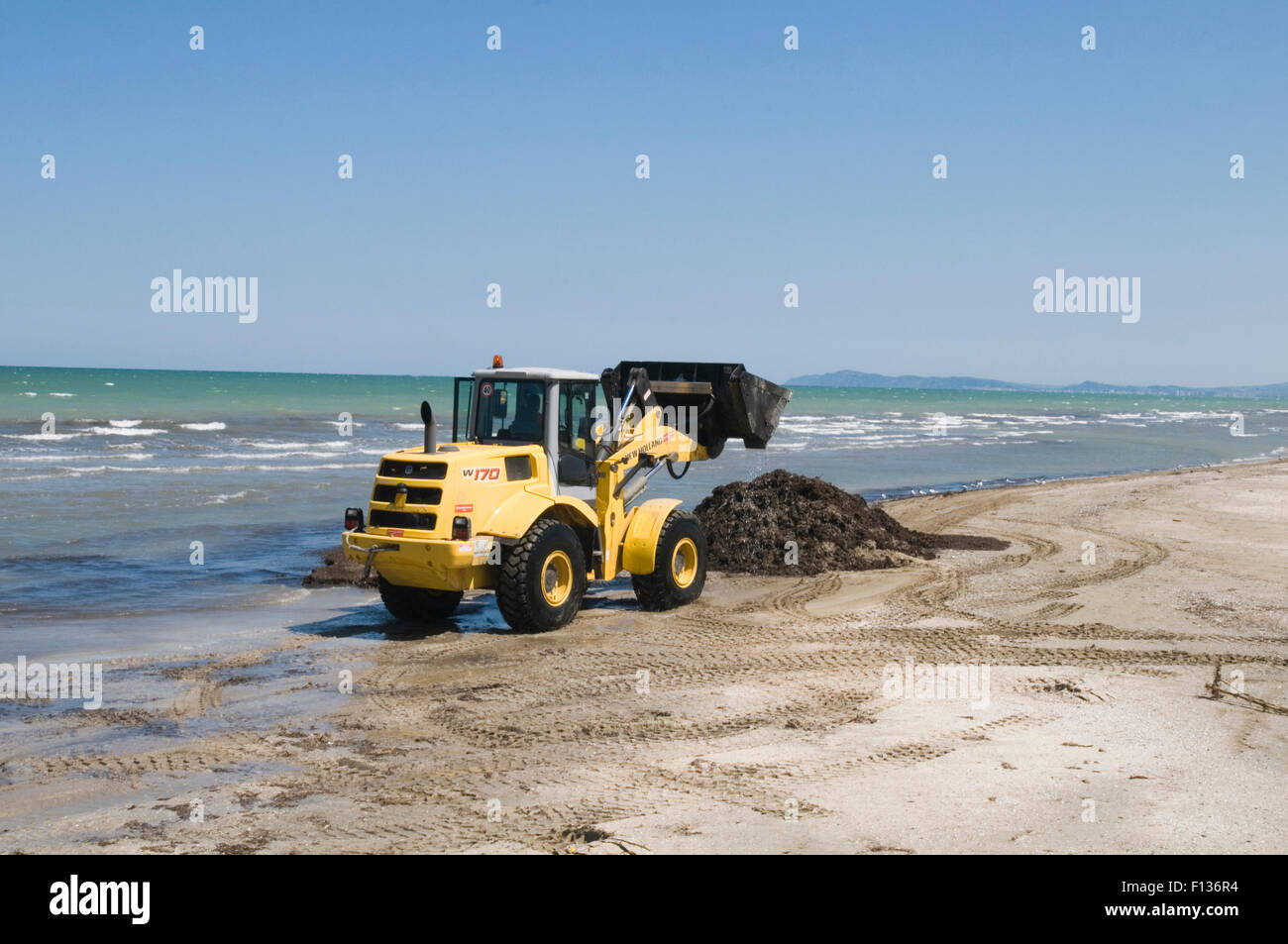 new holland digger diggers earth mover movers excavator earthmovers earthmover big yellow dig digging an hole bucket - Stock Image