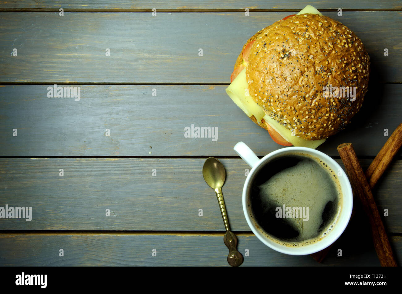 Coffee and wholegrain sandwich roll on a wooden table with copy space Stock Photo