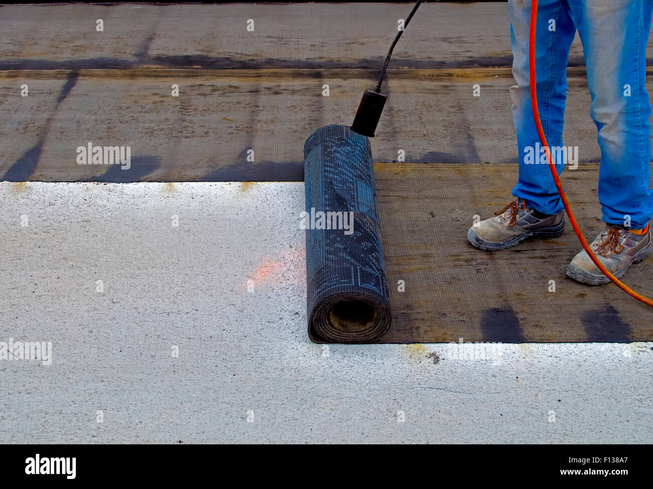 Worker preparing part of bitumen roofing felt roll for melting by gas heater torch flame - Stock Image