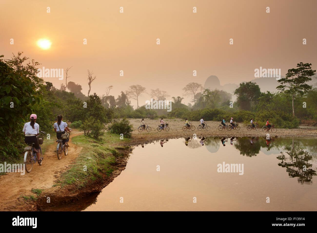 Cyclists riding bikes along riverside path at dawn, near Vang Vieng, Laos, March 2009. - Stock Image