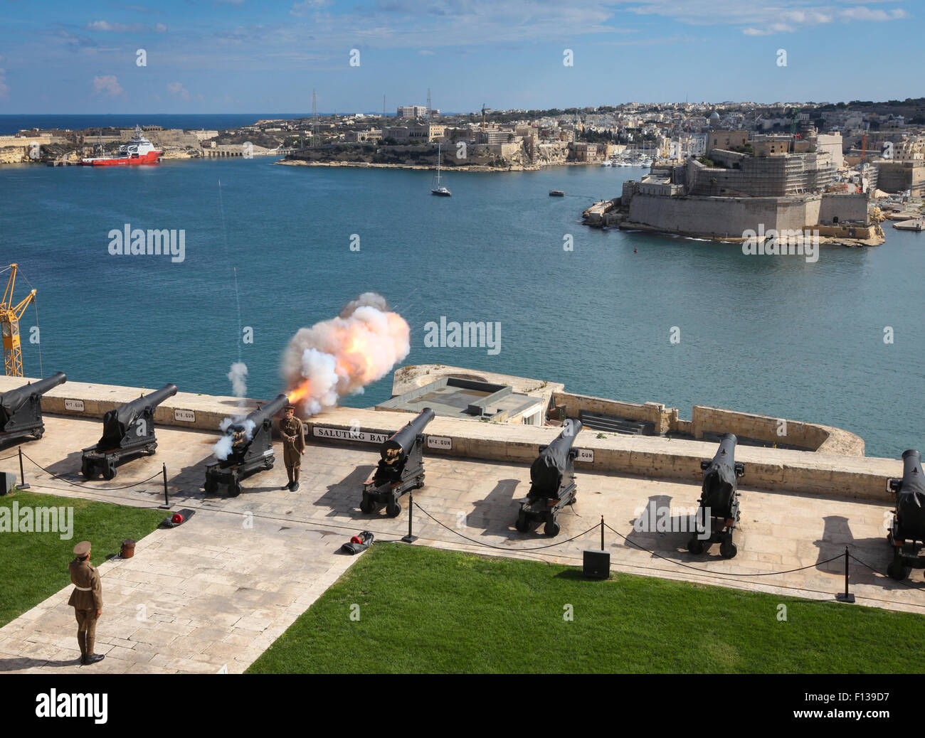 Firing the noon day gun at Saluting Battery, Upper Barracca Gardens, and Grand Harbour, Valletta, Malta - Stock Image