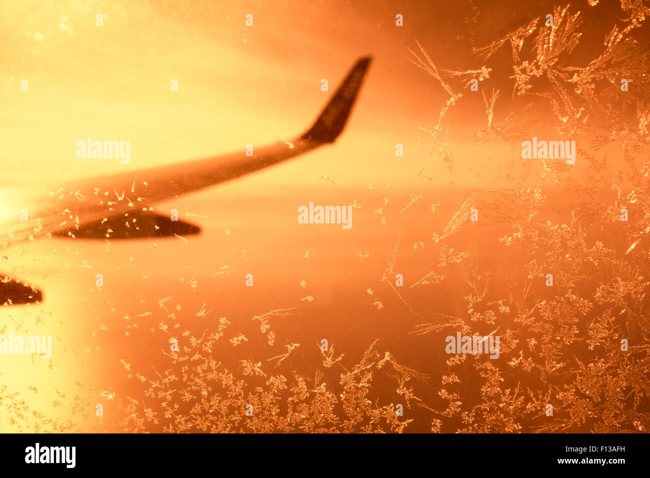 View out of frosted airplane window at sunset Stock Photo
