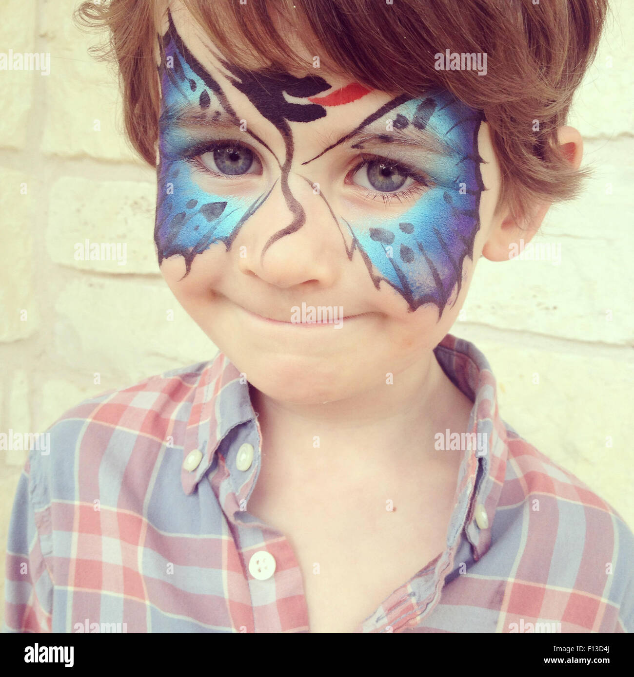 Portrait of a boy with a butterfly face paint - Stock Image