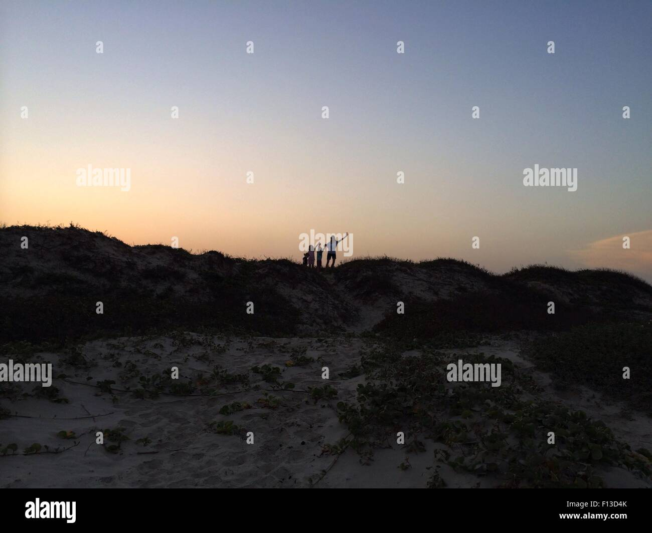 Silhouette of four people standing on a sand dune - Stock Image