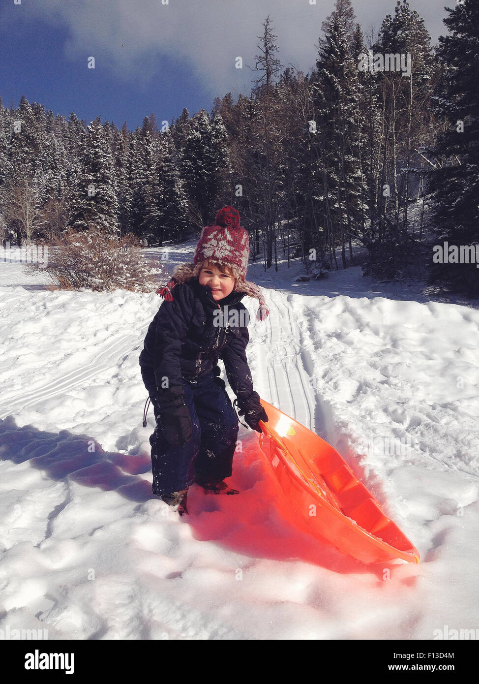 Boy sledding in the snow - Stock Image