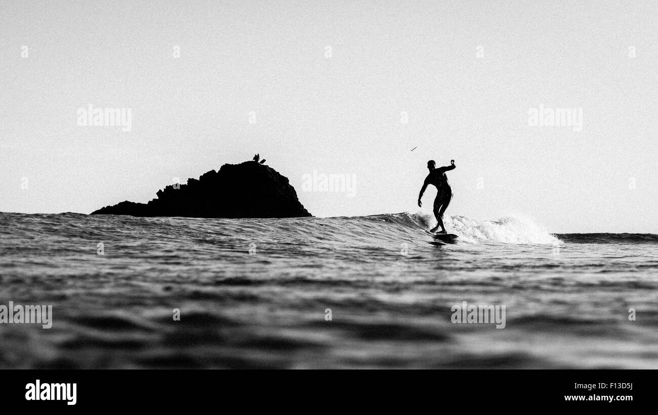 Silhouette of a man surfing Stock Photo