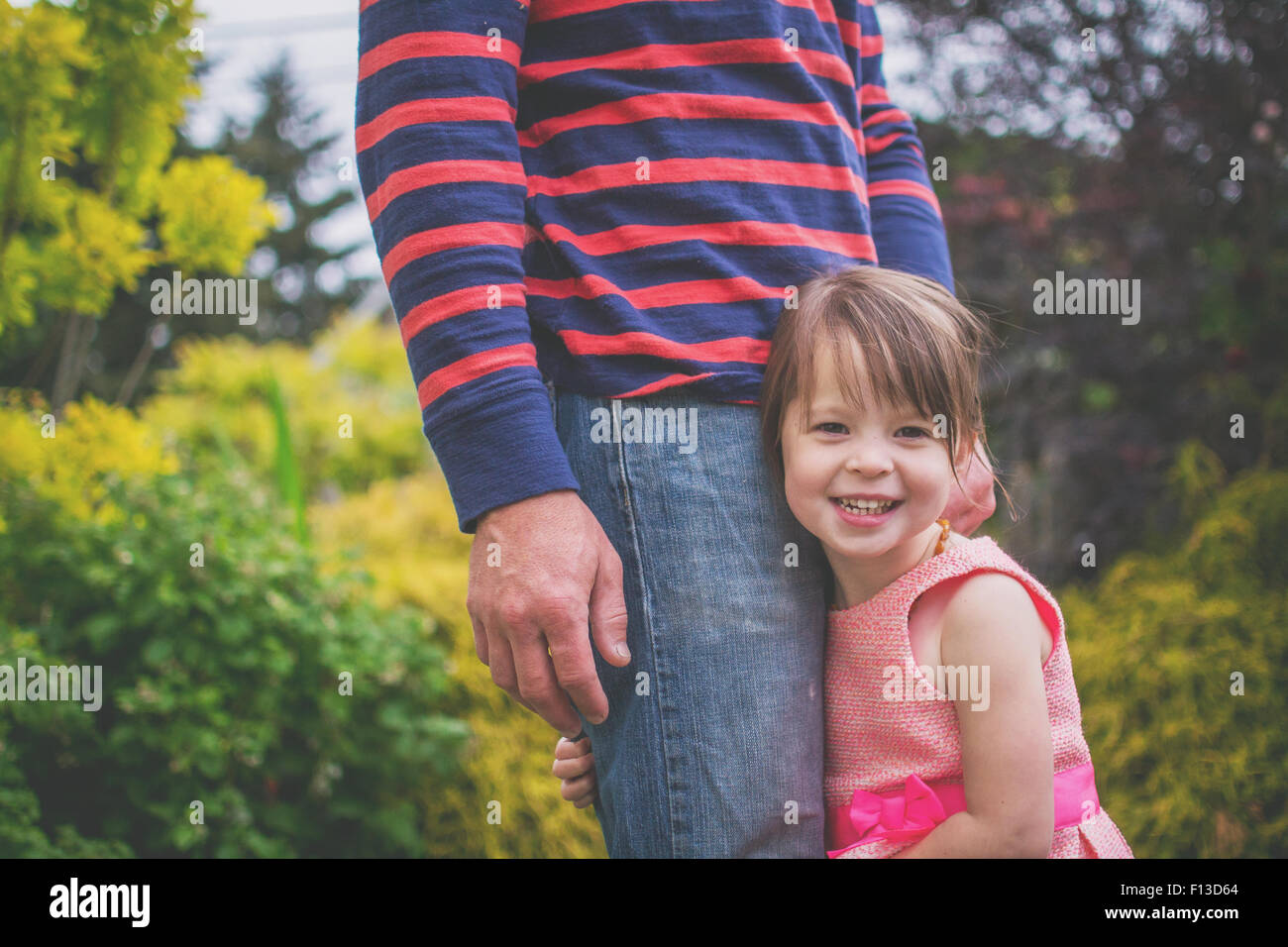 Close-up of a Smiling girl hugging father's leg - Stock Image