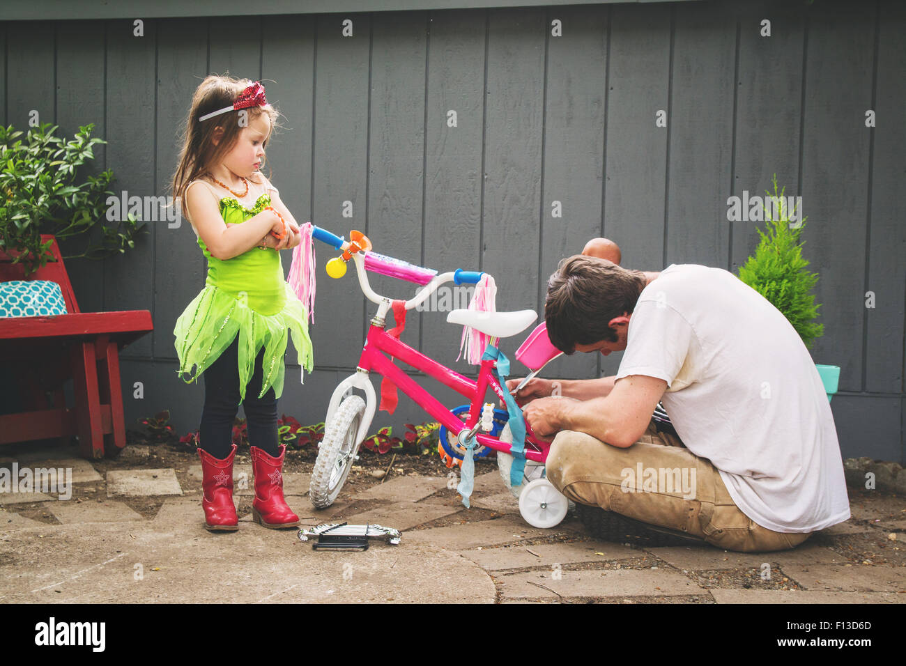 Father mending his daughter's bicycle - Stock Image