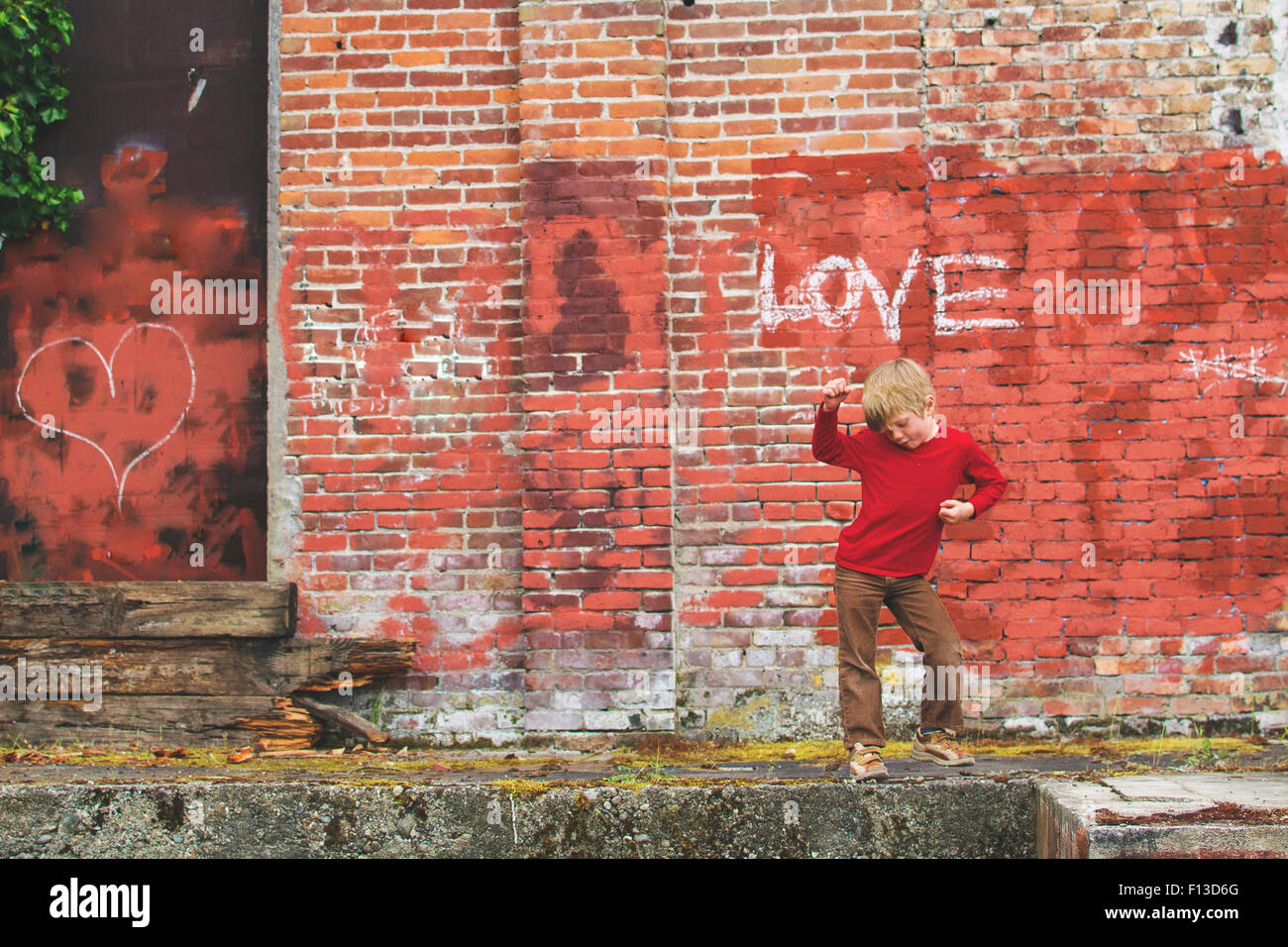 Boy posing in front of wall with graffiti - Stock Image