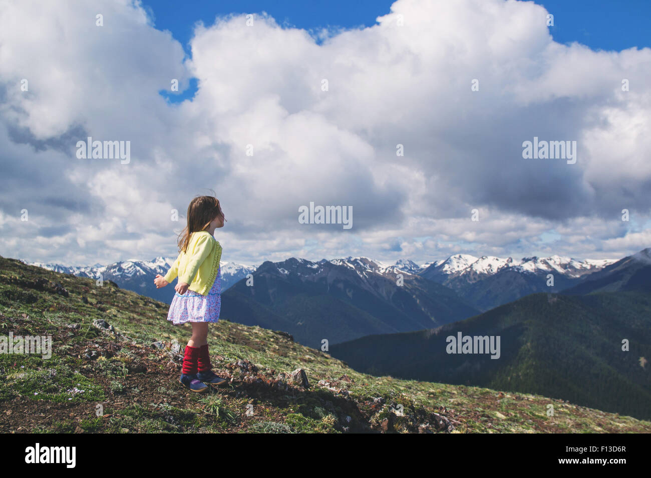 Little girl standing on mountain with arms outstretched - Stock Image