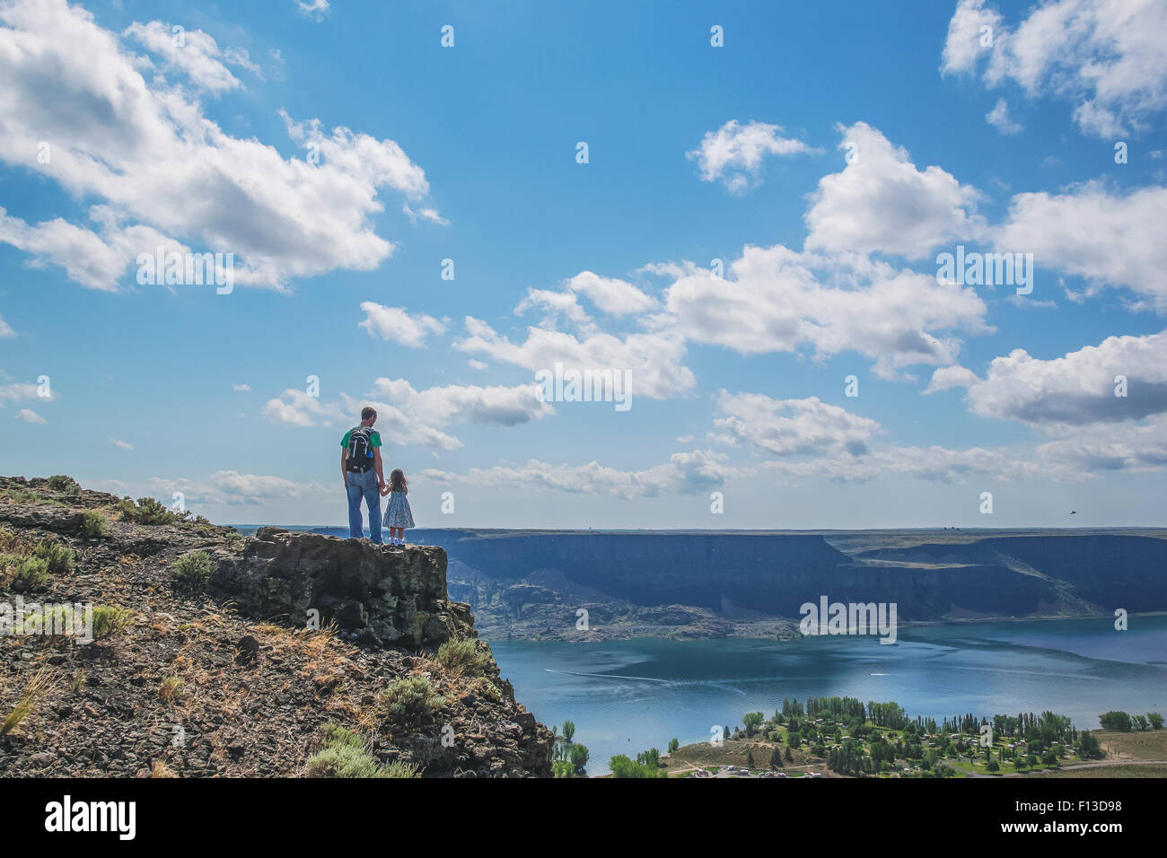 Rear view of father and daughter standing on top of a mountain - Stock Image
