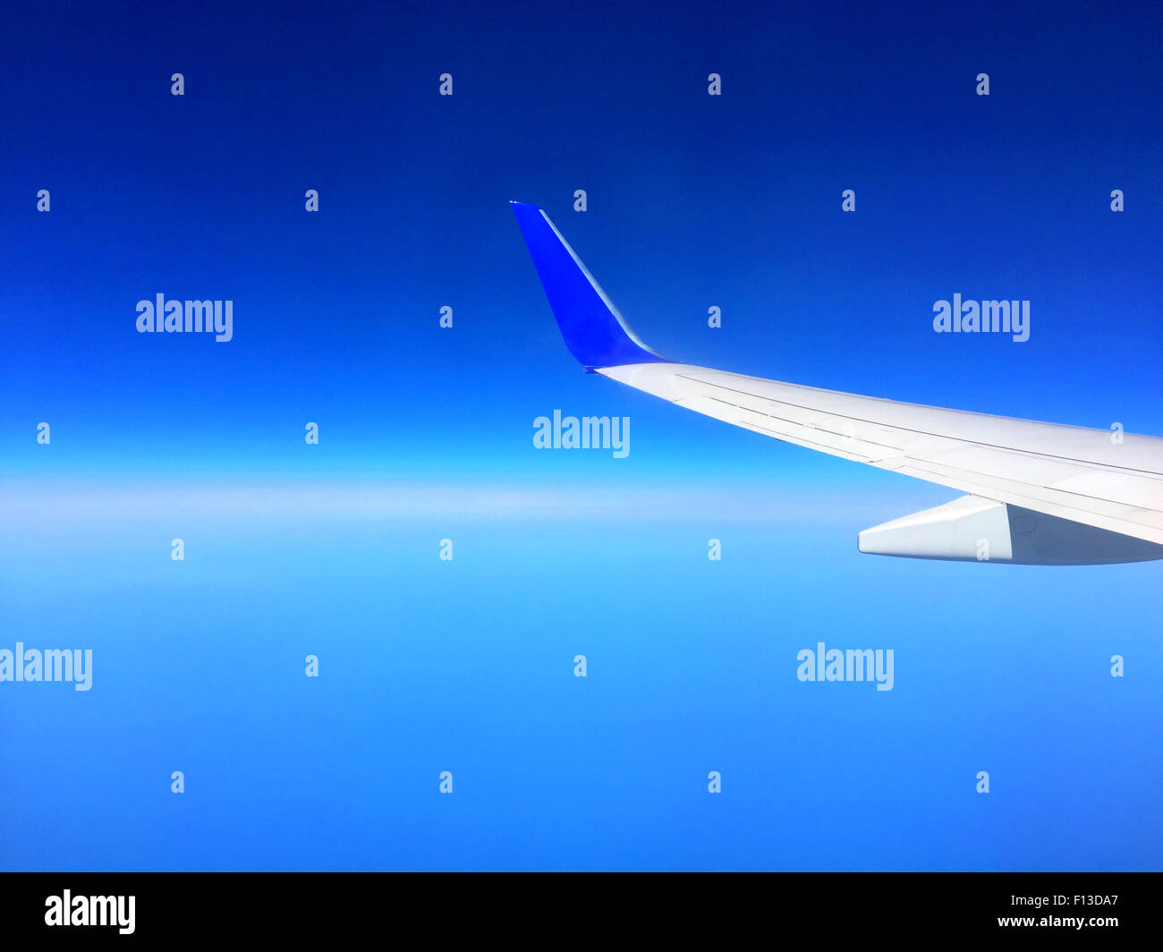 Airplane wing and blue sky - Stock Image