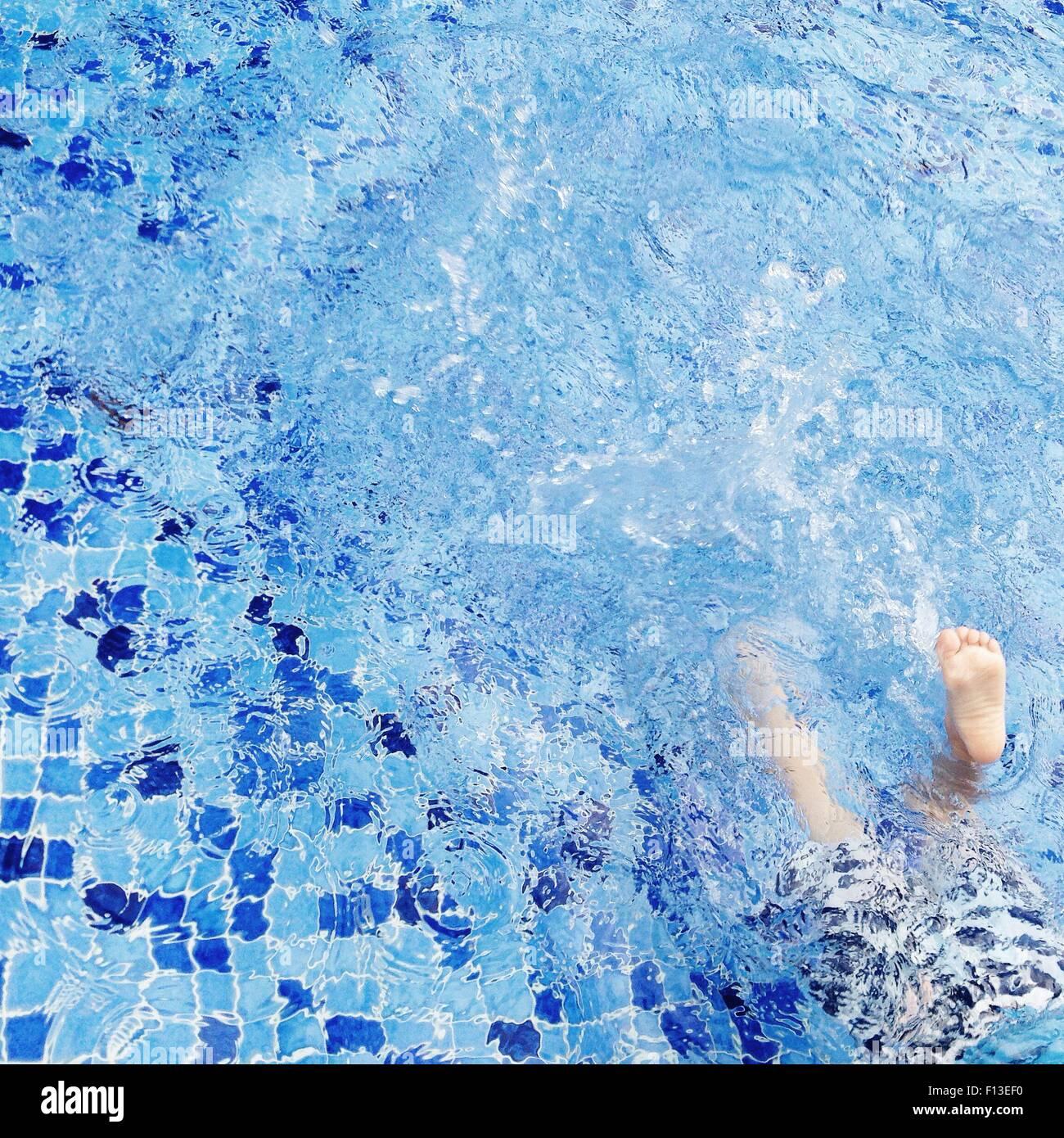 Boy splashing in swimming pool - Stock Image