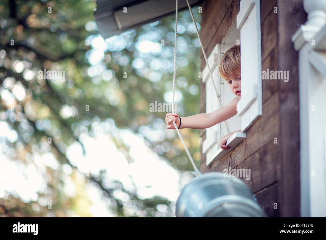 Boy pulling a bucket up to his treehouse Stock Photo