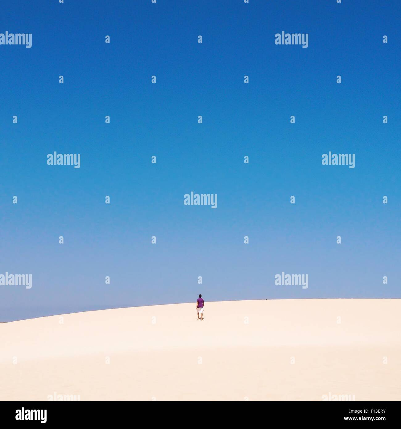 Man walking up a sand dune Stock Photo