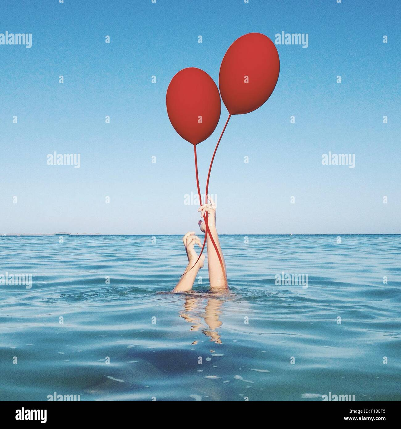 Human hands coming out of the sea holding two balloons - Stock Image