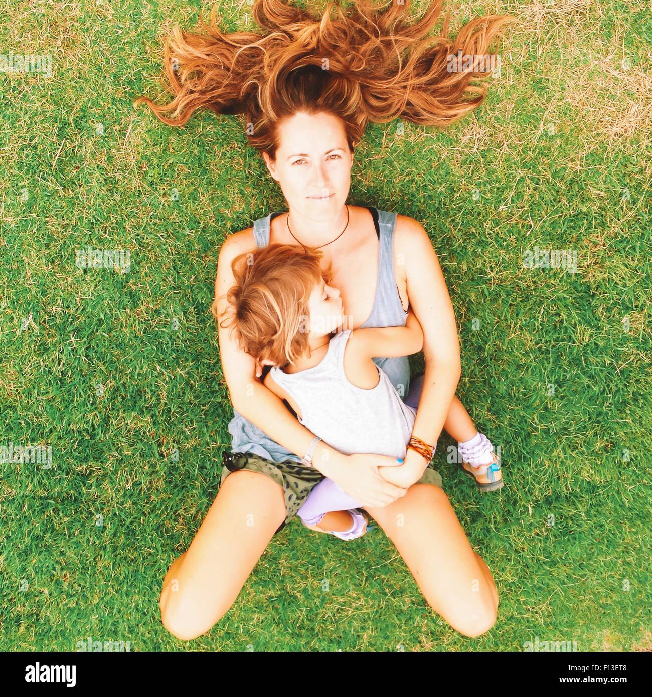 Overhead view of a woman lying on grass with her daughter - Stock Image