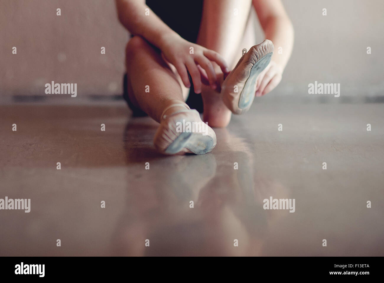Close-up of a girl putting on ballet shoes - Stock Image