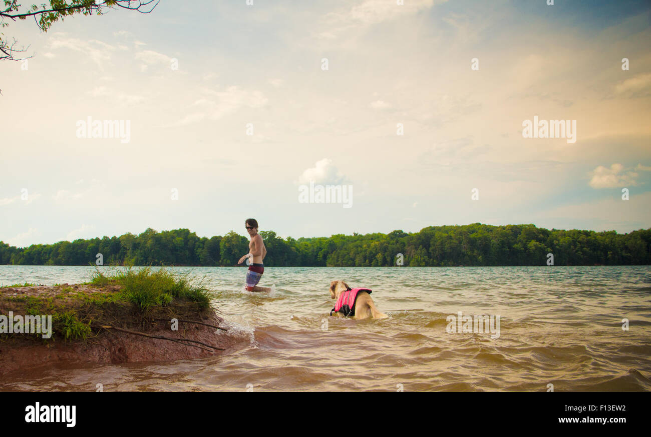 Man and dog walking in a lake, Loudon, Tennessee, USA - Stock Image