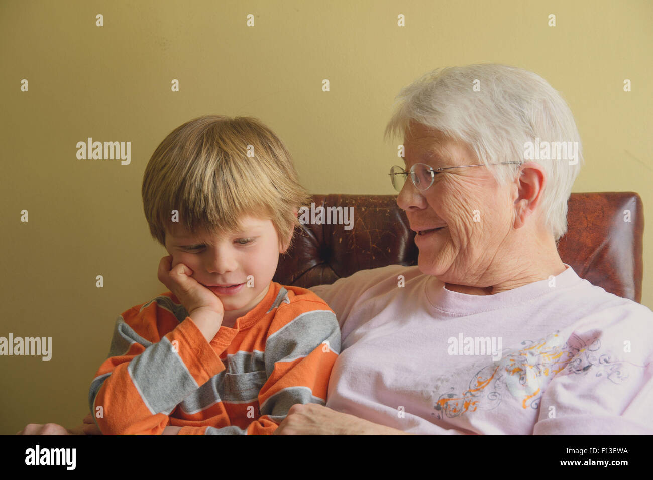 Boy sitting with his grandmother - Stock Image