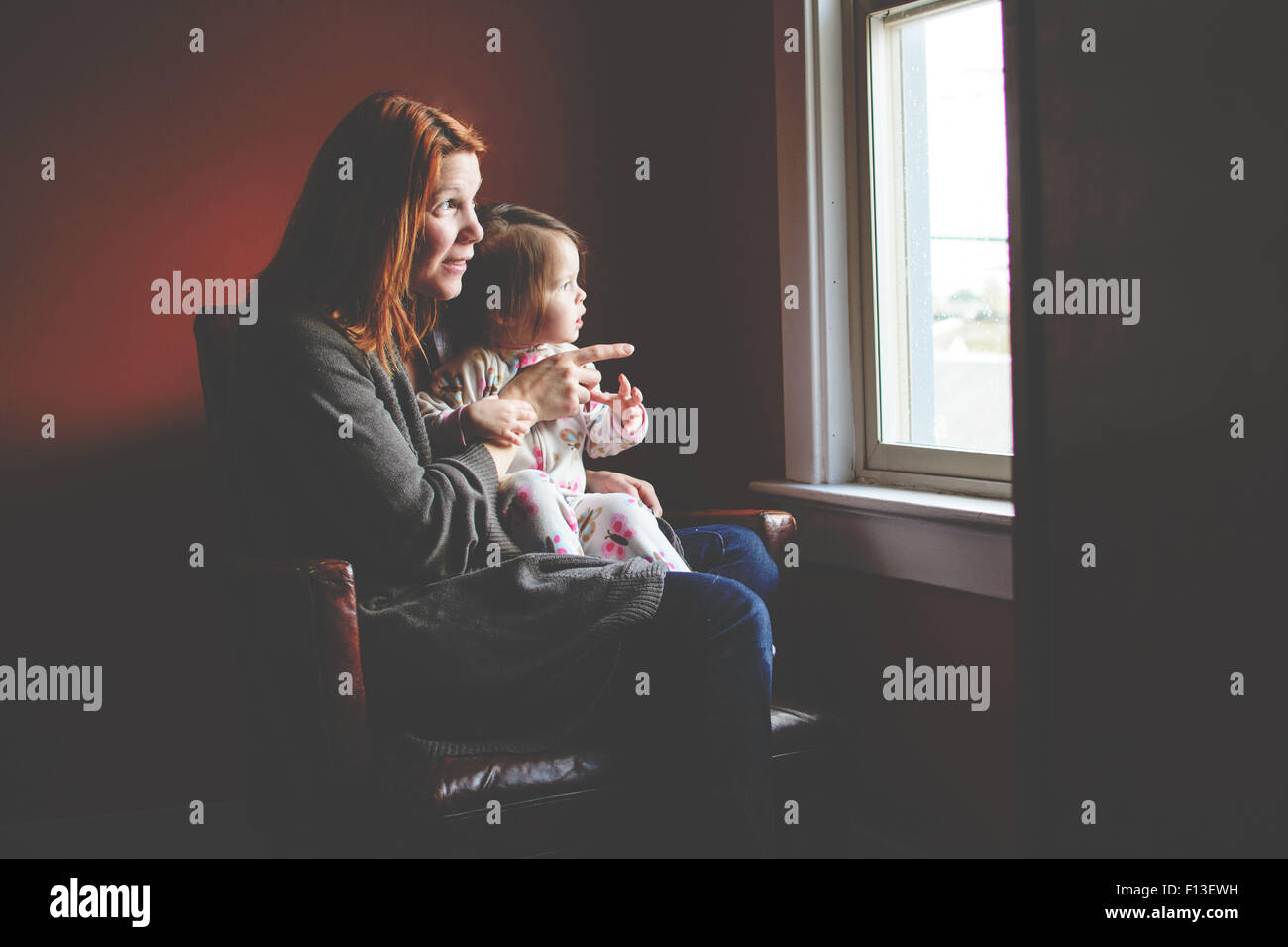 Baby girl sitting on her mother's lap, looking out the window - Stock Image