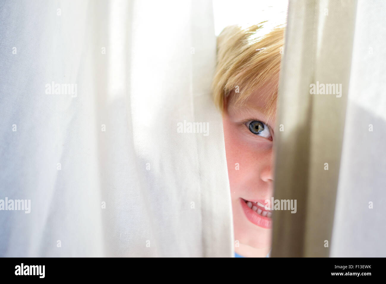 Boy looking out from behind a curtain - Stock Image