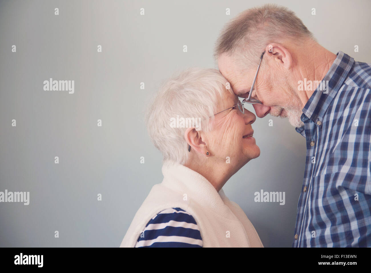 Senior couple touching foreheads and smiling - Stock Image