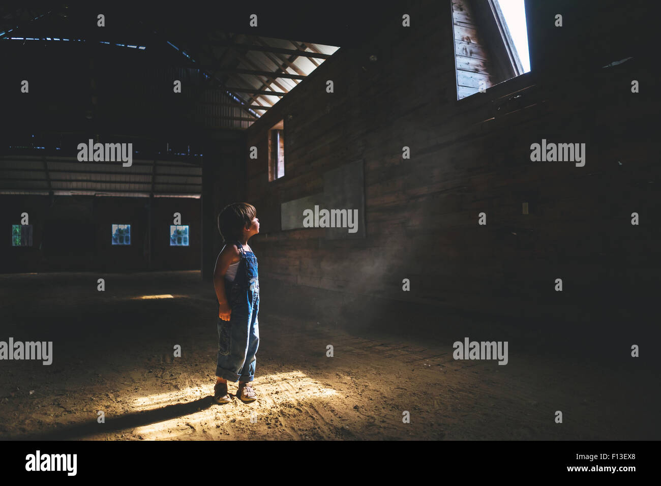 Boy looking up at a window in a barn - Stock Image