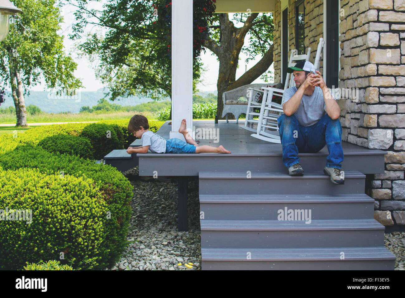 Man sitting on porch steps looking at son Stock Photo