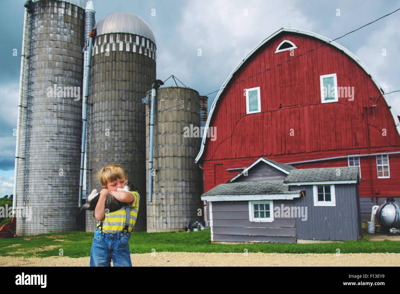 Boy cuddling a cat on a farm - Stock Image