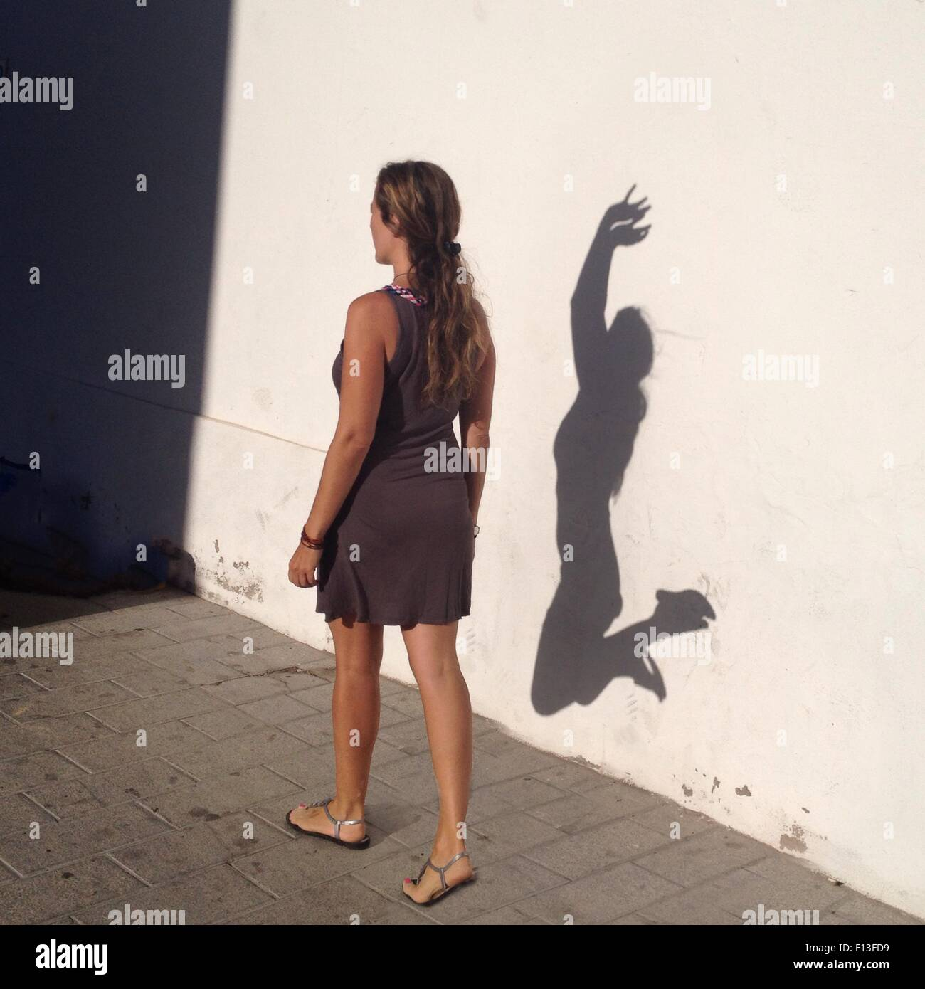 Woman walking with an alter ego shadow jumping for joy - Stock Image