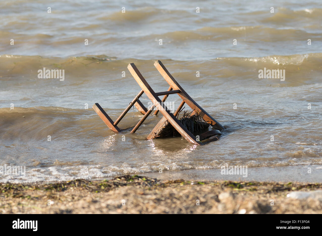 Polluted beach with a chair in it. - Stock Image