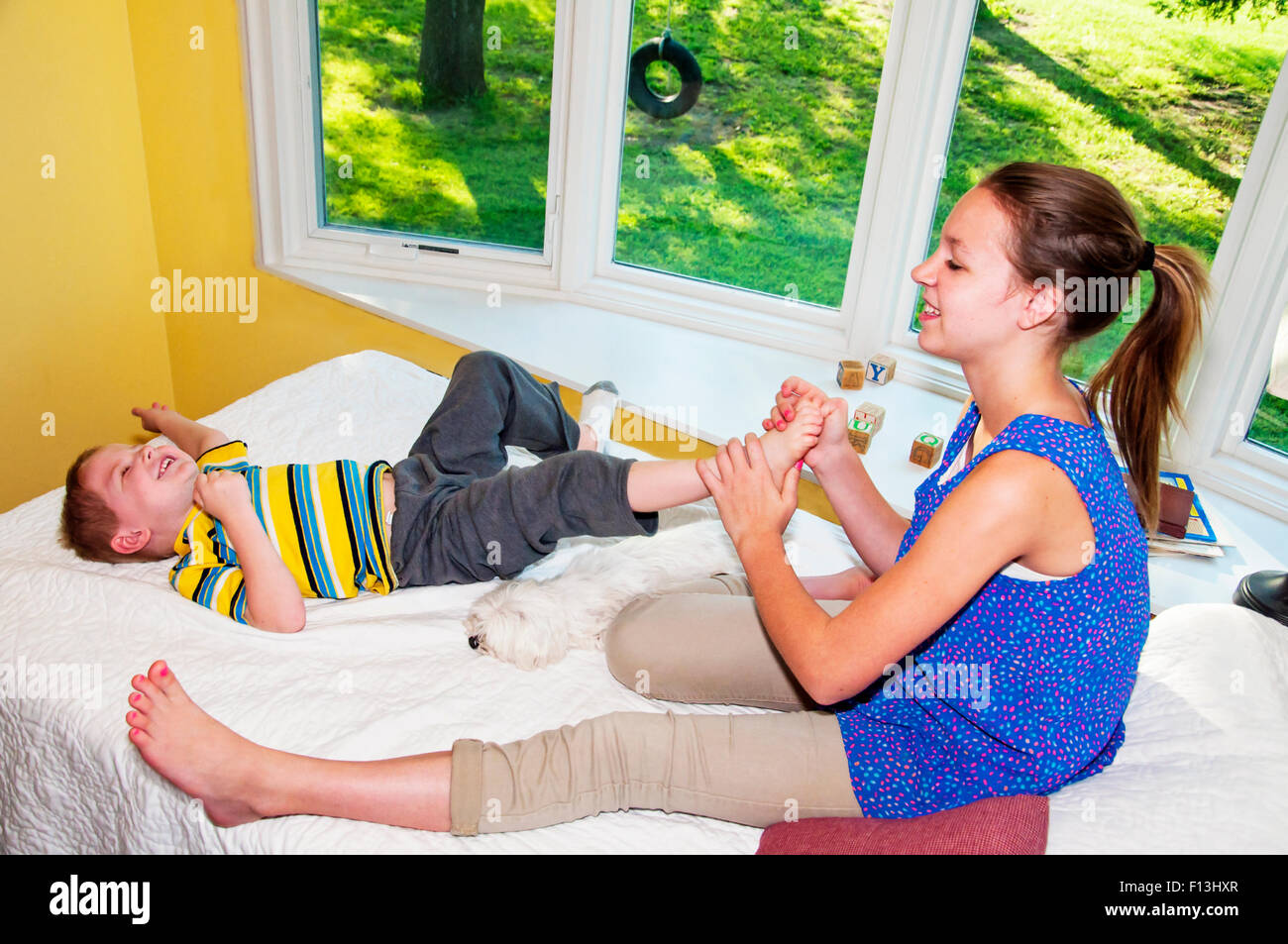Child wiggling away while foot tickled by sister Stock Photo