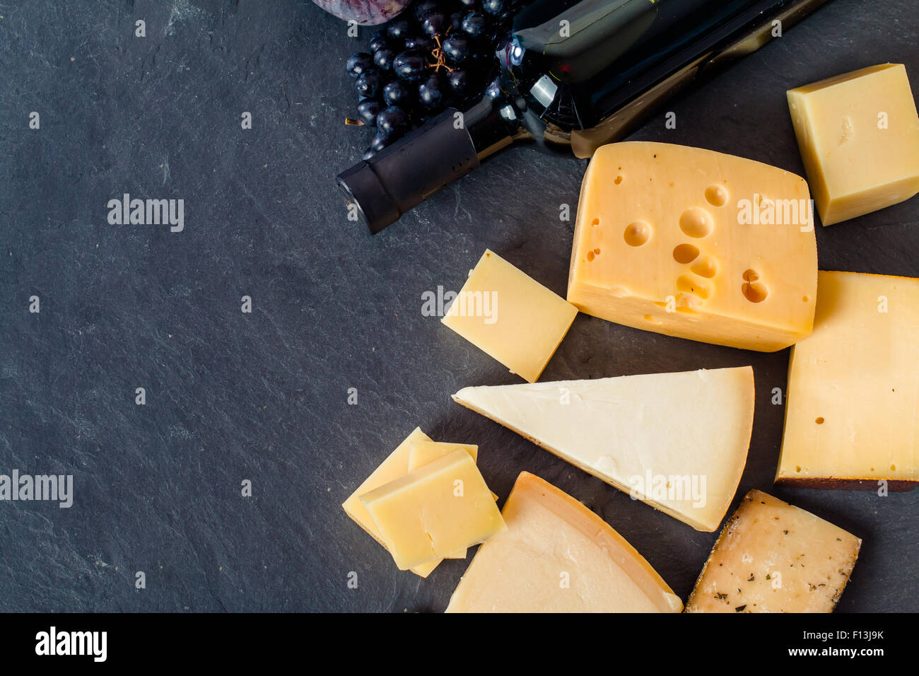 Different types of cheeses, red wine, grapes and figa on black board, top view Stock Photo