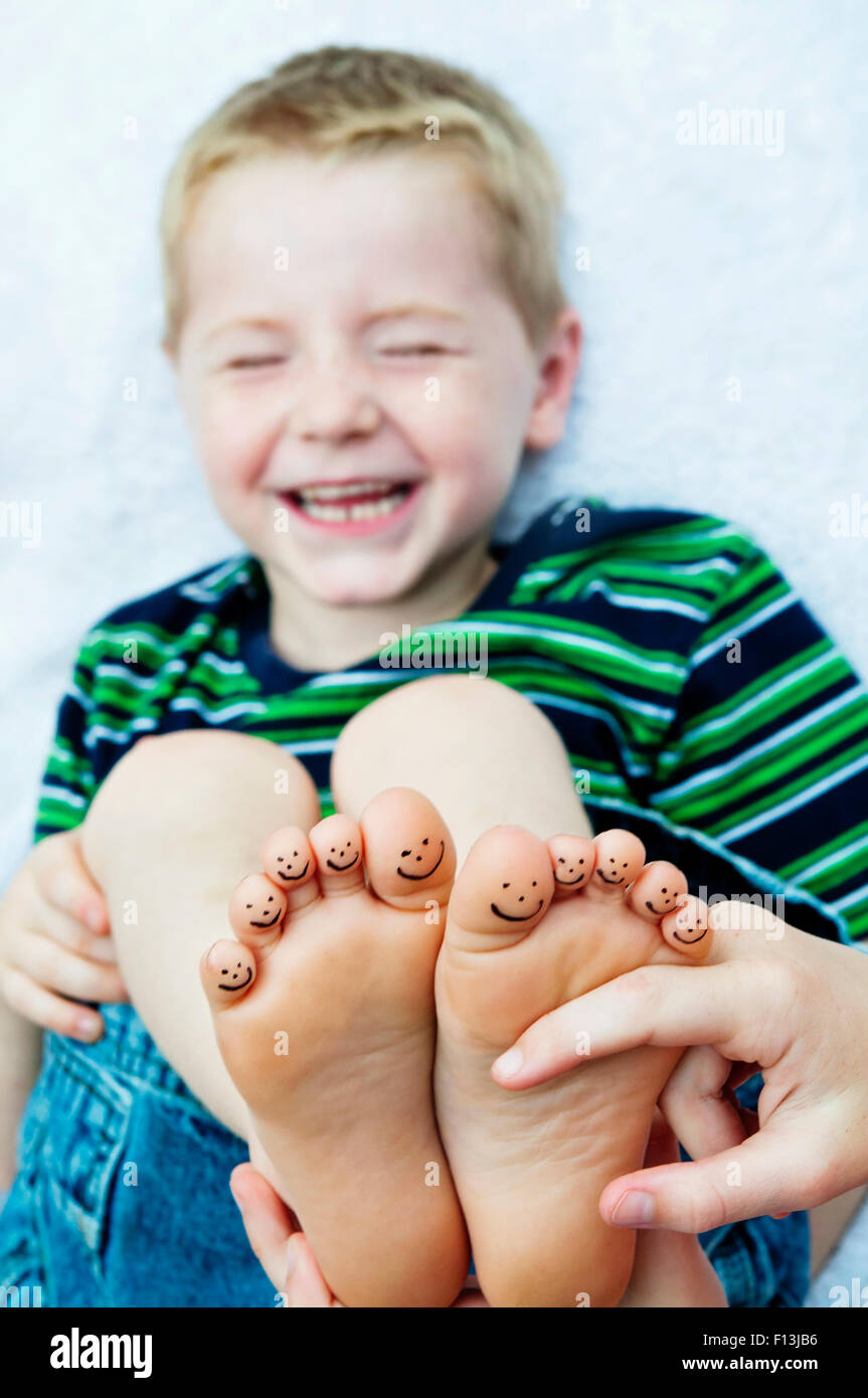 boy laying down getting barefeet tickled smiley toes - Stock Image