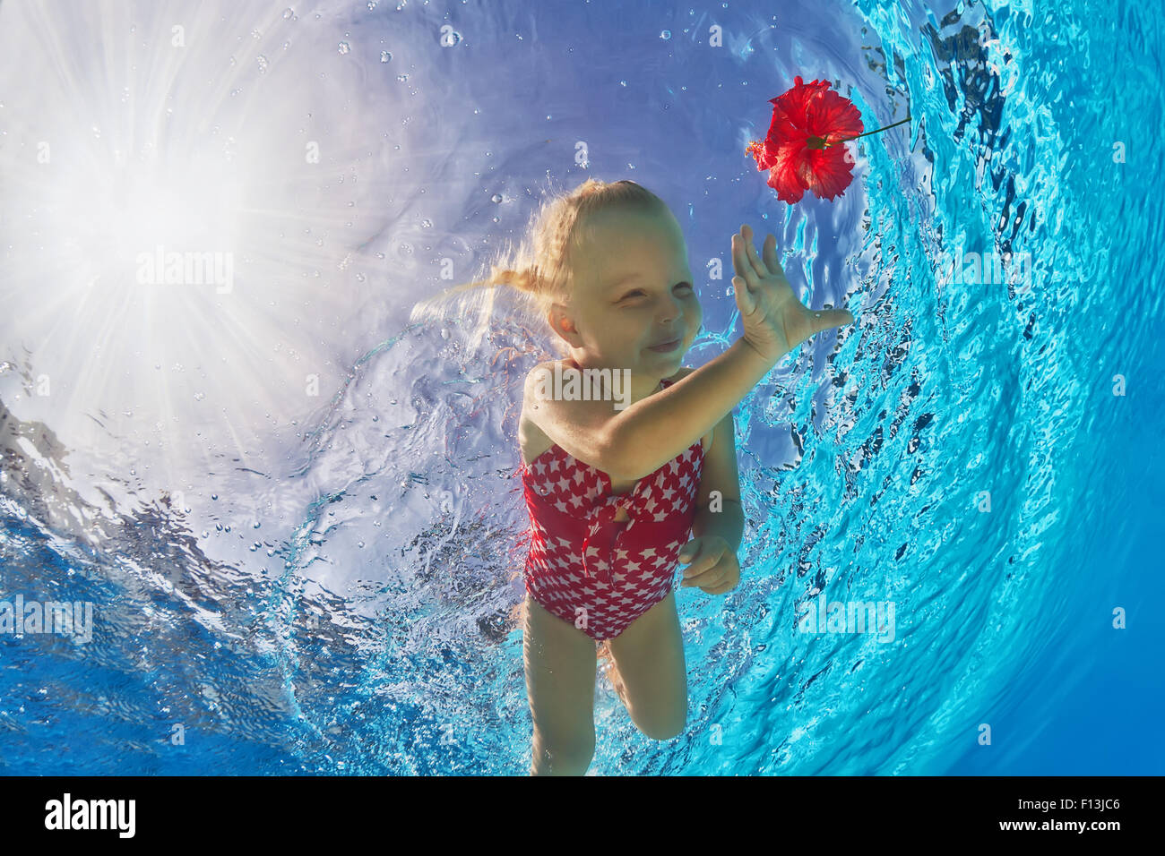 Happy little baby with smile and open eyes diving in swimming pool with clear blue water for a bright red flower. Stock Photo